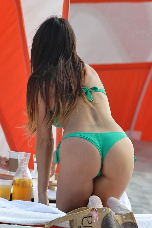Italian model Claudia Romani seen relaxing on the beach with a friend and posing for some tourists in Miami