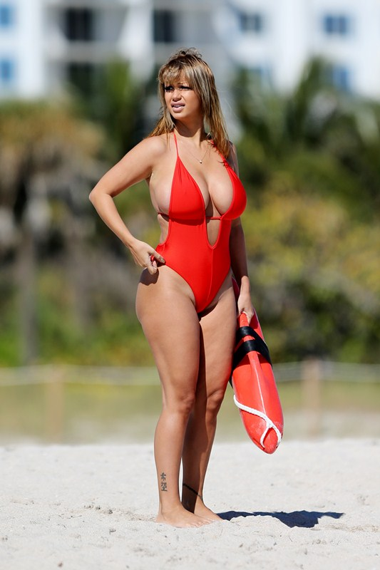 Plus model Jolena Forde busts out of her Baywatch babe red one-piece bathing suit as she rescues Russian rapper GeeGun Denis Ustimenko-Vainstein filming his new music video in Miami Beach, Florida