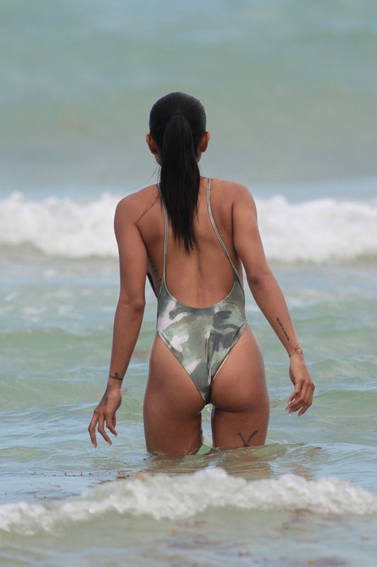 Karrueche Tran looks relaxed and happy as she heats up the beach in a sexy green camouflage one piece