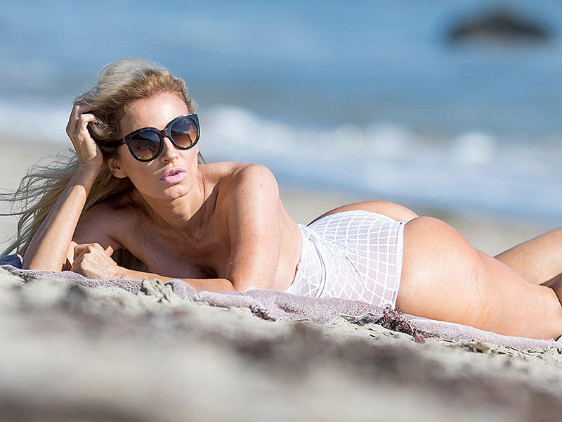 Brazilian Playmate Ana Braga shows off her curves in a sheer swimsuit on the beach in Malibu