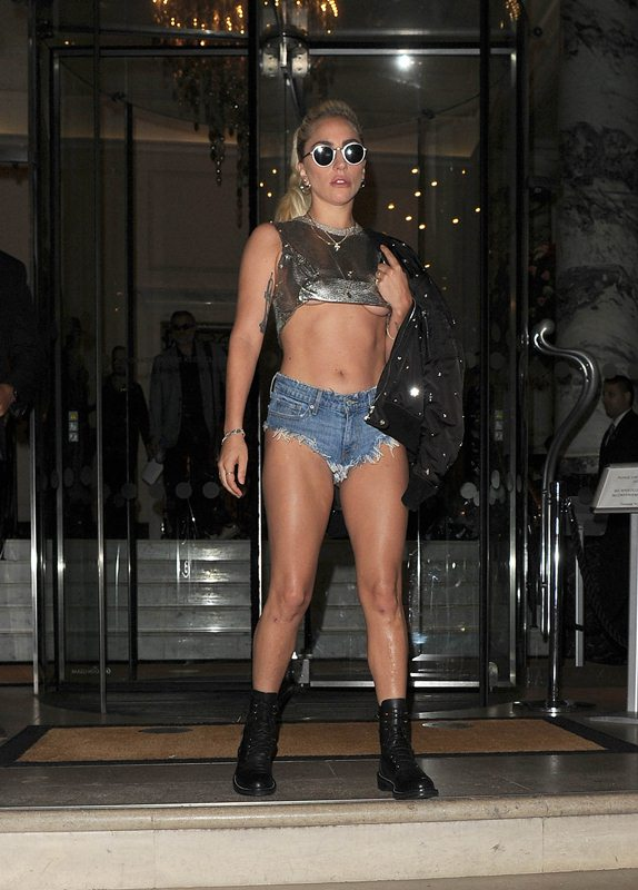 Lady Gaga leaves her hotel in a typically eye catching outfit of a gold crop trop and denim hot pants